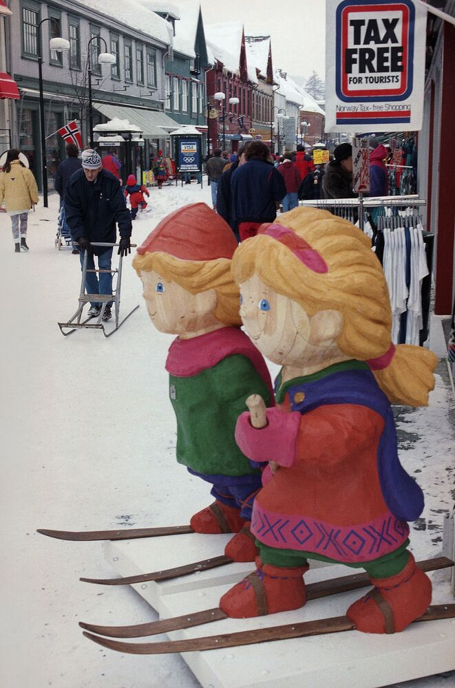 The wooden mascots of the Winter Olympics watch over one of the main shopping streets in Lillehammer, Norway in 1994.