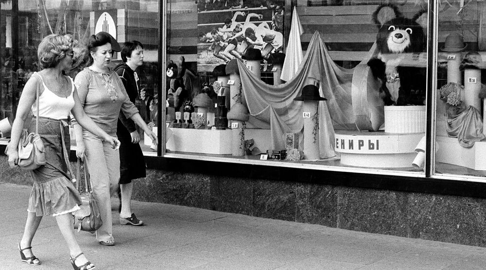 Shoppers walk past a store window that displays Misha the Bear Cub, the 1980 Moscow Olympic mascot, and other Olympic souvenirs in downtown Moscow.