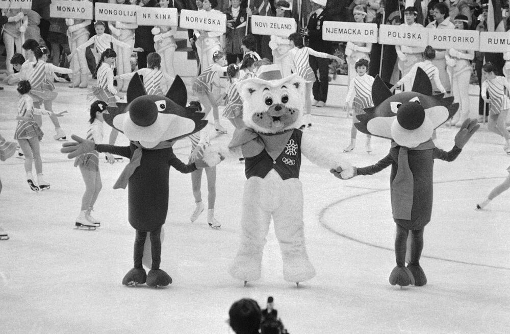 Vucko the Wolf, the symbol for the 14th winter Olympic Games in Sarajevo's Yugoslavia, dances with Howdy the bear who was the symbol for the upcoming  Winter Games, held in Calgary, Canada at the closing ceremonies for the games in Sarajevo. The ceremony was held at Zetra Arena in 1984.