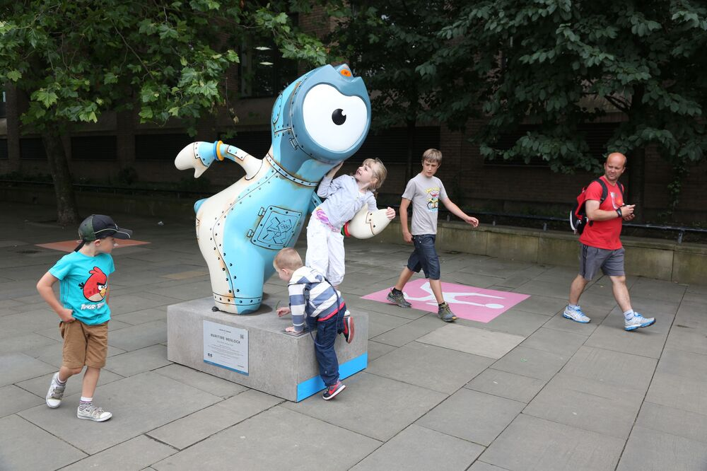 The 2012 London Olympic mascot Wenlock is surrounded by kids who are thoroughly examining the creature.