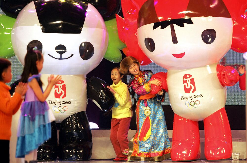 Girls dance with the mascots for the 2008 Olympic Games at an unveiling ceremony in Beijing 11 November 2005. On that day, celebrities and public figures attended the glittering extravaganza to announce the five different mascots as the capital marked the 1,000 days-to-go before the Olympic Games begin here.