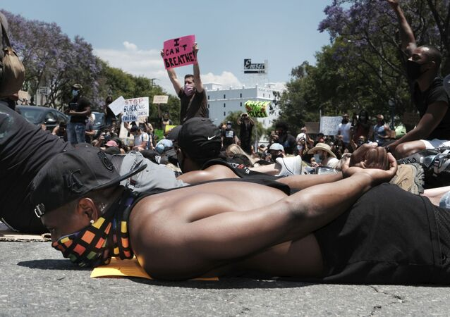 Devion Coleman joins LGBTQ community members and Black Lives Matter protesters as they lay on the street with their hands on their backs in West Hollywood, Calif. on Wednesday, June 3, 2020, over the death of George Floyd, a black man who died in police custody in Minneapolis on Memorial Day