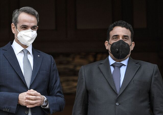 Greek Prime minister Kyriakos Mitsotakis (L) poses Libya's presidential council chairman Mohammad Younes Menfi (R) prior to their meeting in Athens on April 14, 2021.