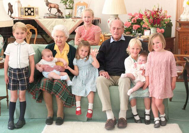 Britain's Queen Elizabeth and Prince Philip sit with Prince George, Prince Louis, Savannah Phillips, Princess Charlotte, Isla Phillips, Lena Tindall, and Mia Tindall in this undated picture released on April 14, 2021.