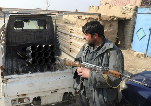 An Afghan security person sand near a vehicle in which rockets were placed, in Bagram, north of Kabul, Afghanistan, Saturday, Dec. 19, 2020.