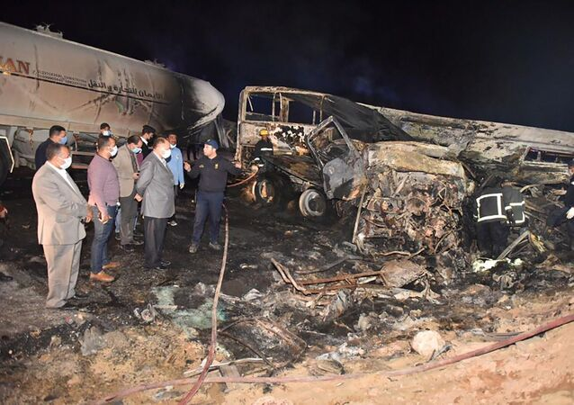 In this photo provided by Assiut Governorate media office, the authorities work on the collision site where a bus overturned Tuesday, while trying to pass a truck on a highway in southern Egypt on Wednesday, April 14, 2021, near the city of Assiut, Egypt.