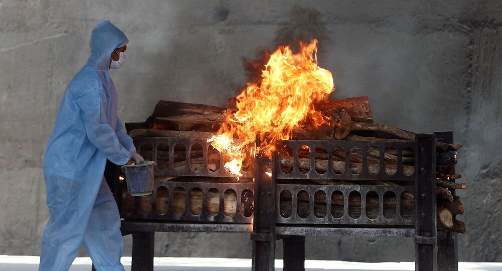 A frontline worker in personal protective equipment (PPE) sprays a flammable liquid on a burning funeral pyre of a man who died from the coronavirus disease  (COVID-19), at a crematorium on the outskirts of Mumbai India, April 15, 2021