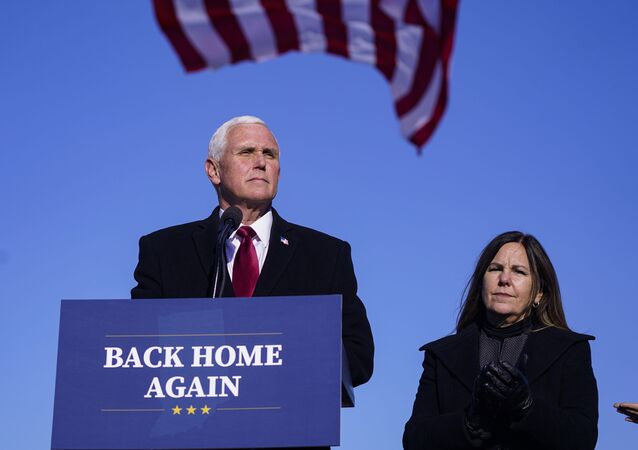 In this Jan. 20, 2021, file phot, former Vice President Mike Pence speaks after arriving back in his hometown of Columbus, Ind., as his wife Karen watches.