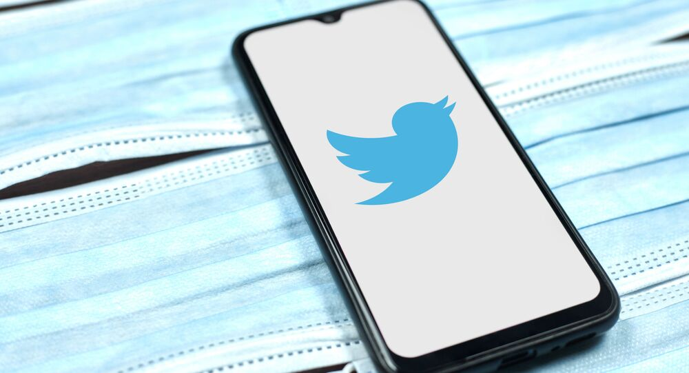 Twitter logo on smartphone screen over the face masks.