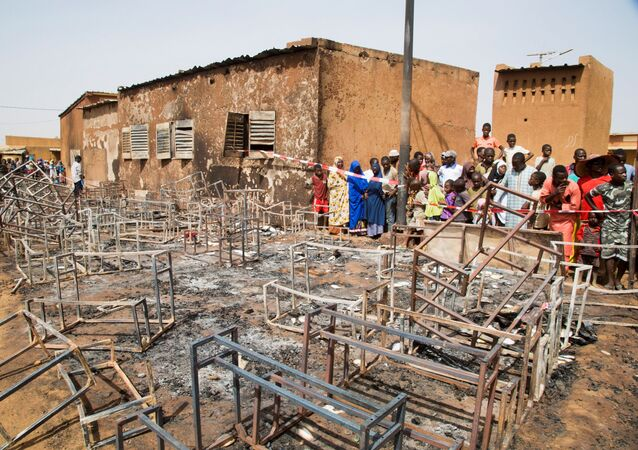 People stand next to the remains of the burnt nursery school in Niamey, Niger April 14, 2021