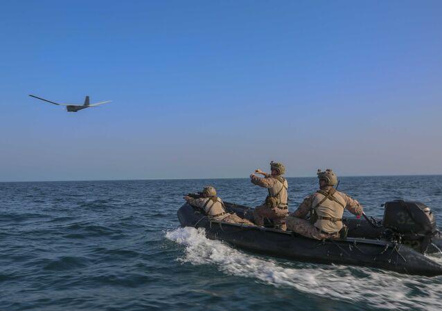 A reconnaissance Marine launches an RQ-20 Puma aboard a combat rubber raiding craft, May 24, 2020