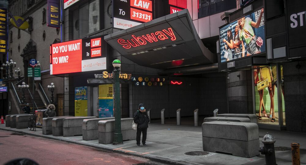 A woman stands alone outside an empty subway entrance on 42nd Street in Times Square, which is usually bustling with activity, in New York, on Wednesday, March 25, 2020.