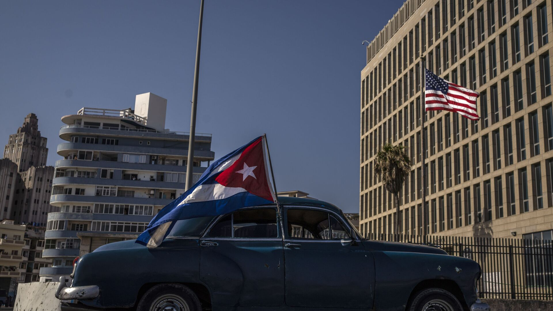 A classic American car flying a Cuban flag drives past the American embassy during a rally calling for the end of the US blockade against the island nation, in Havana, Cuba, Sunday, March 28, 2021. - Sputnik International, 1920, 14.09.2021