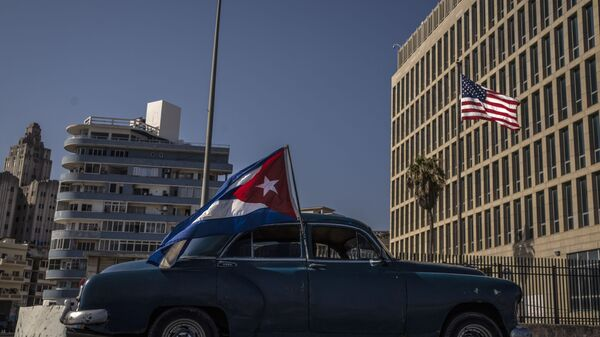 A classic American car flying a Cuban flag drives past the American embassy during a rally calling for the end of the US blockade against the island nation, in Havana, Cuba, Sunday, March 28, 2021. - Sputnik International
