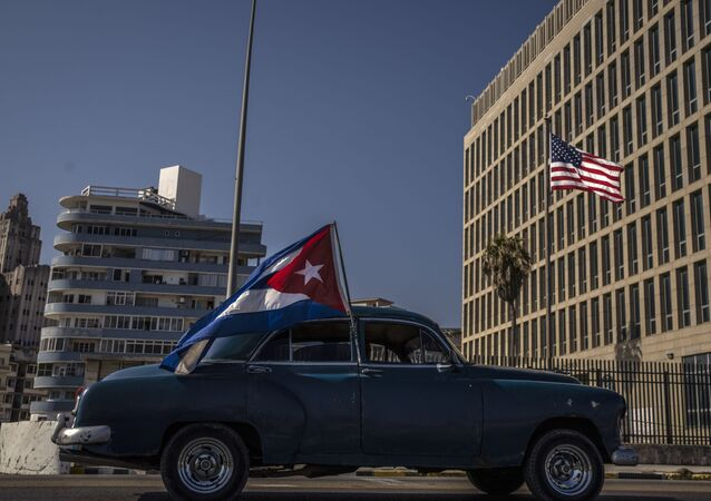 A classic American car flying a Cuban flag drives past the American embassy during a rally calling for the end of the US blockade against the island nation, in Havana, Cuba, Sunday, March 28, 2021.