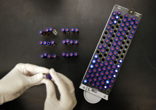In this Aug. 10, 2015, photo, Christine Jelinek, a postdoctoral fellow at Johns Hopkins University, works alongside a tray of vials containing cerebral spinal fluid in Baltimore. Dr. Akhilesh Pandey, a researcher at Johns Hopkins University, said his research analyzes both adult and fetal tissue, and by identifying which proteins are present, he can get clues that could be used to help detect cancer in adults earlier.