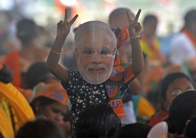 A supporter of Bharatiya Janata Party (BJP) wearing a face cutout of Indian Prime Minister Narendra Modi attends a public rally being addressed by him during the ongoing fourth phase of the West Bengal's state legislative assembly elections, at Kawakhali on the outskirts of Siliguri on April 10, 2021.