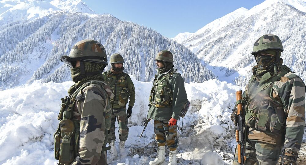 Indian army soldiers stand on a snow-covered road near Zojila mountain pass that connects Srinagar to the union territory of Ladakh, bordering China on February 28, 2021.