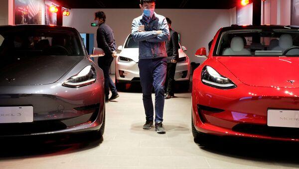 A man wearing a face mask following the coronavirus disease (COVID-19) outbreak walks by Tesla Model 3 sedans and Tesla Model X sport utility vehicle at a new Tesla showroom in Shanghai, China May 8, 2020. - Sputnik International