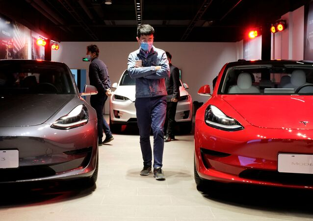 A man wearing a face mask following the coronavirus disease (COVID-19) outbreak walks by Tesla Model 3 sedans and Tesla Model X sport utility vehicle at a new Tesla showroom in Shanghai, China May 8, 2020.