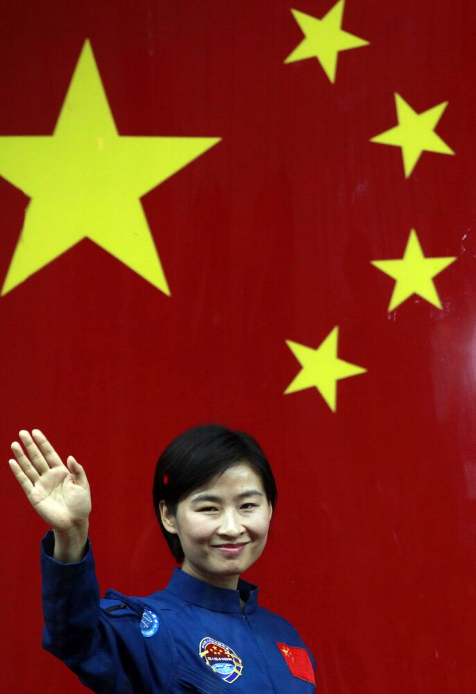 In this file photo taken Friday, 15 June 2012, Liu Yang, China's first female astronaut, waves as she leaves an event to meet the press at the Jiuquan satellite launch center near Jiuquan in the land-locked province of Gansu in western China.