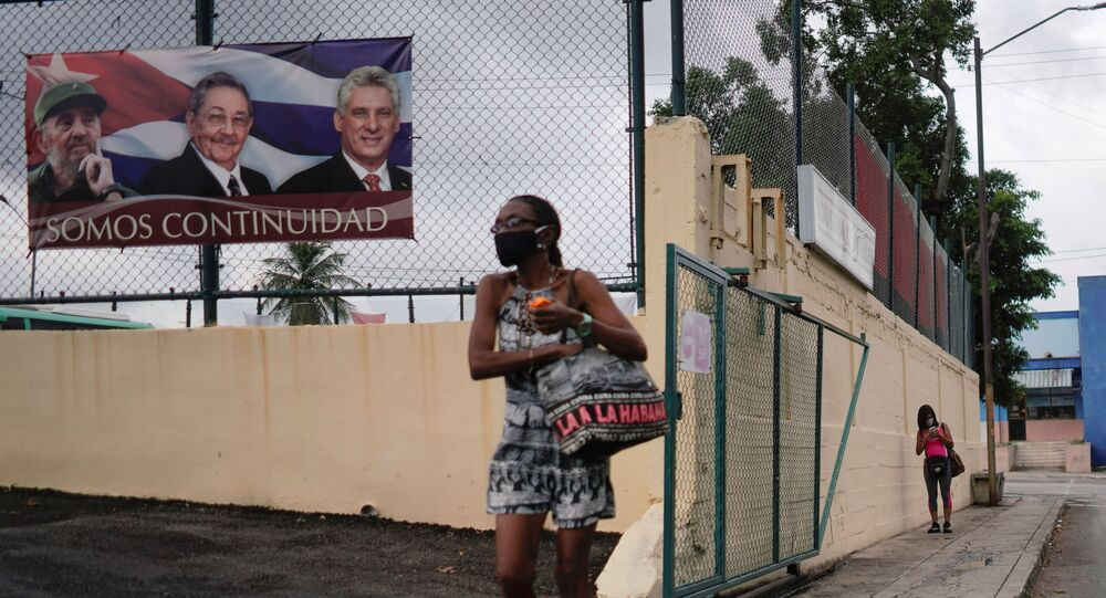 A woman passes by a poster displaying images of late Cuban President Fidel Castro, Cuba's First Secretary of the Communist Party and former President Raul Castro and Cuba's President Miguel Diaz Canel with a sign that reads: We are continuity, in Havana, Cuba, April 12, 2021