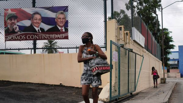 A woman passes by a poster displaying images of late Cuban President Fidel Castro, Cuba's First Secretary of the Communist Party and former President Raul Castro and Cuba's President Miguel Diaz Canel with a sign that reads: We are continuity, in Havana, Cuba, April 12, 2021 - Sputnik International