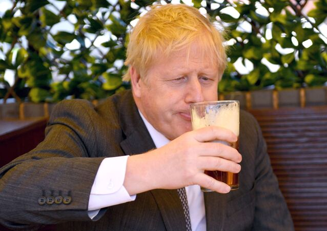 Prime Minister Boris Johnson sips a pint in the beer garden during a visit to The Mount Tavern Pub and Restaurant on the local election campaign trail in Wolverhampton, West Midlands, 19 April 2021