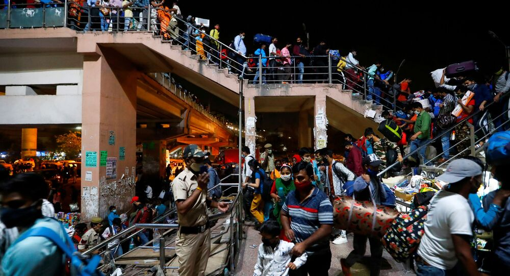 Migrant workers arrive at a bus station to board buses to return to their villages after Delhi government ordered a six-day lockdown to limit the spread of the coronavirus disease (COVID-19), in Ghaziabad on the outskirts of New Delhi, India, April 19, 2021.