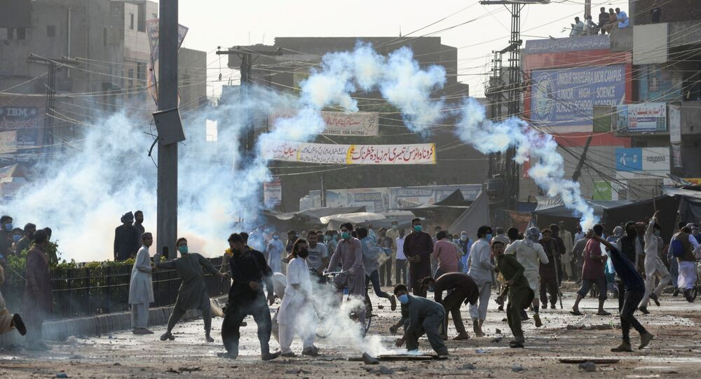 Supporters of the Tehreek-e-Labaik Pakistan (TLP) Islamist political party throwback tear gas canisters fired by police during a protest against the arrest of their leader in Lahore, Pakistan April 13, 2021.