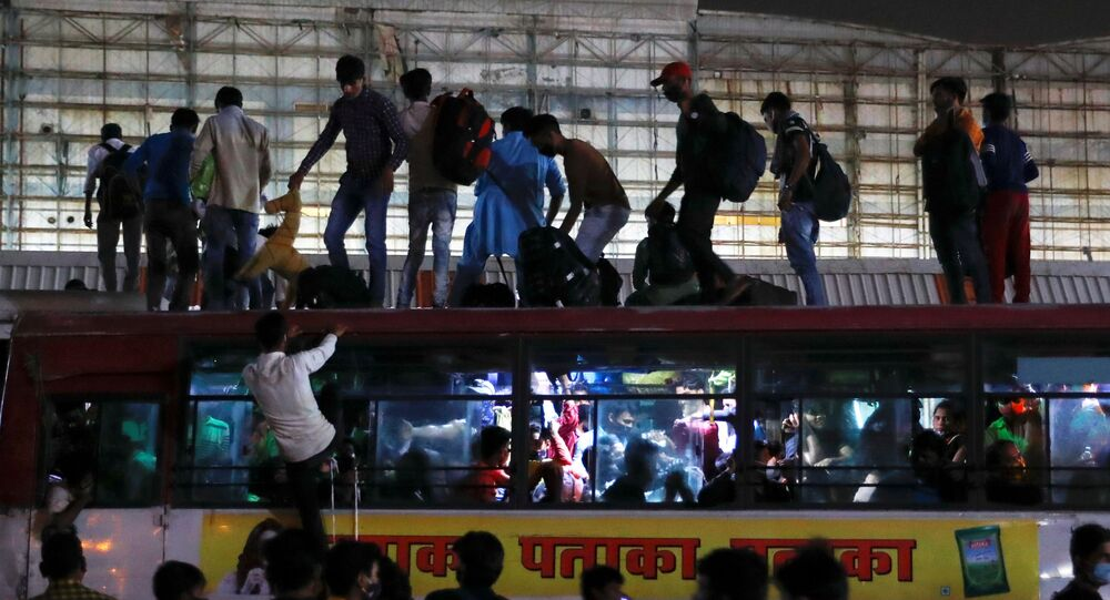 Migrant workers stand on top of an overcrowded bus to return to their villages after Delhi government ordered a six-day lockdown to limit the spread of the coronavirus disease (COVID-19), in Ghaziabad on the outskirts of New Delhi, India, April 19, 2021.
