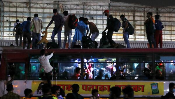 Migrant workers stand on top of an overcrowded bus to return to their villages after Delhi government ordered a six-day lockdown to limit the spread of the coronavirus disease (COVID-19), in Ghaziabad on the outskirts of New Delhi, India, April 19, 2021. - Sputnik International