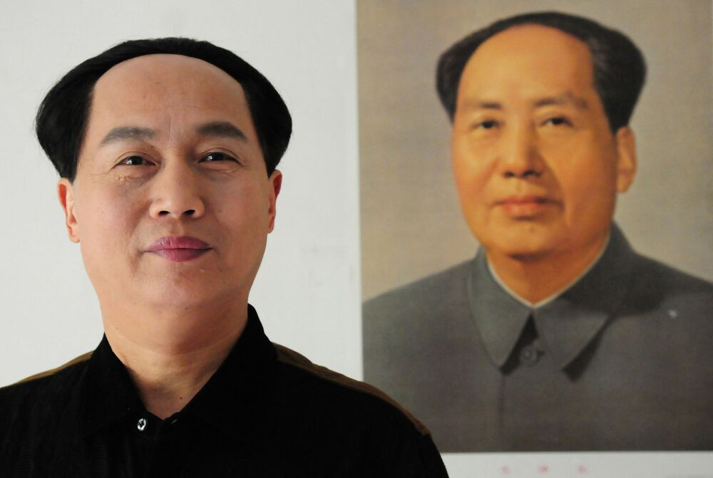 58-year-old Chinese actor Xu Ruilin (L) poses in front of a picture of the founding father of Communist China, Mao Zedong.