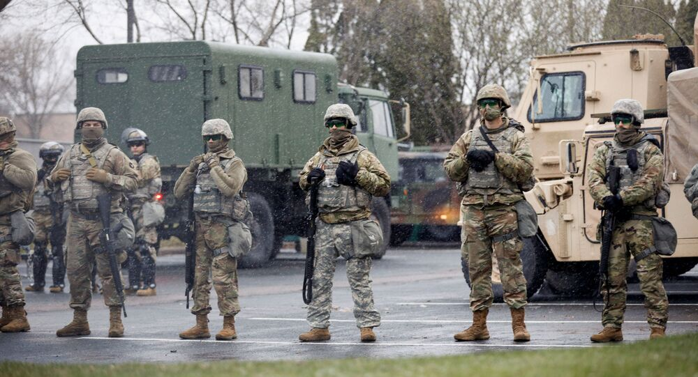 National Guard members stand guard as demonstrators rally days after Daunte Wright, 20, was shot and killed by former Brooklyn Center Police Officer Kim Potter, in Brooklyn Center, Minnesota, 13 April 2021