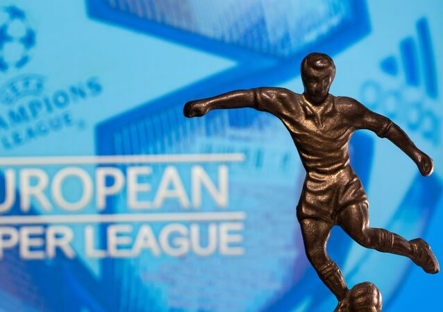 A metal figure of a football player with a ball is seen in front of the words European Super League and the UEFA Champions League logo in this illustration taken April 20, 2021