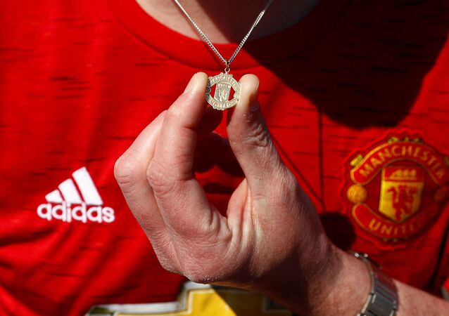 A Manchester United fan holds their Manchester United logo necklace outside Old Trafford as twelve of Europe's top football clubs launch a breakaway Super League - Manchester, Britain - April 19, 2021