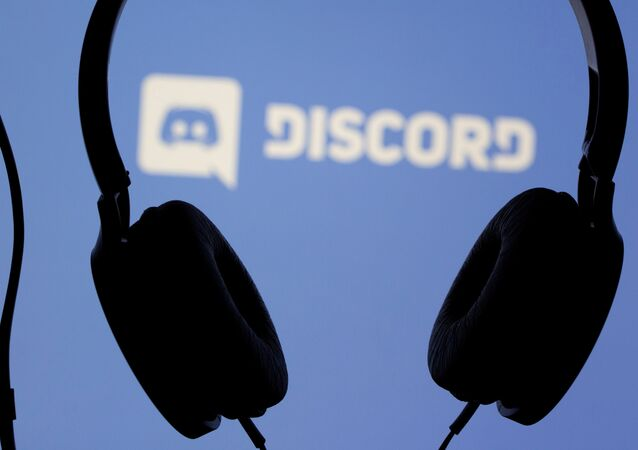 Headphones are seen in front of displayed Discord app logo in this illustration taken March 29, 2021.
