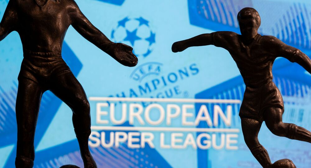 Metal figures of football players are seen in front of the words European Super League and the UEFA Champions League logo in this illustration taken April 20, 2021.
