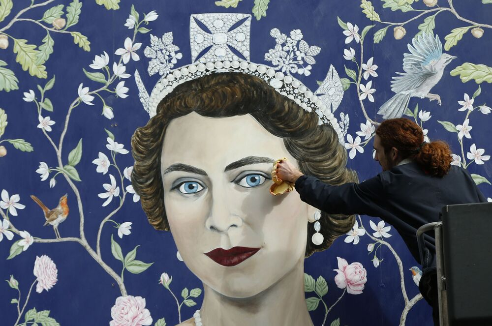 Workmen install a new mural by Frederick Wimsett of Queen Elizabeth II to mark her 90th birthday celebrations, in central London, 2016.