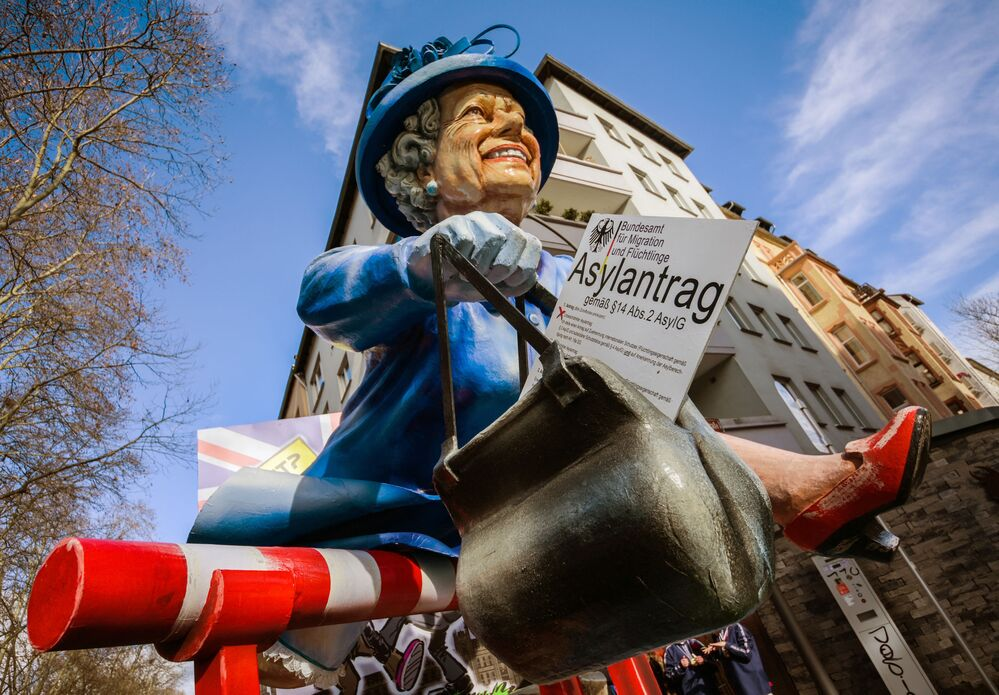 The Queen is depicted as an asylum seeker on a carnival float during the Rose Monday Carnival street parade in Mainz, Germany, in 2019.