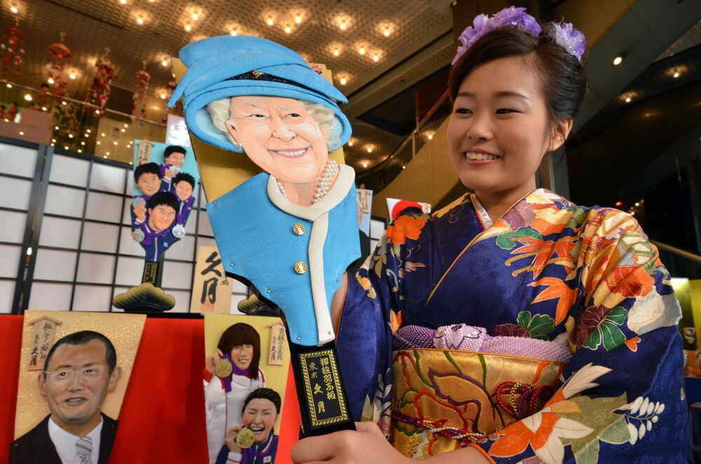 An employee of Japanese doll maker Kyugetsu wearing a kimono dress displays an ornamental wooden racket or hagoita decorated with this 2012 headline makers, Britain's Queen Elizabeth II, at the company's showroom in Tokyo in 2012.