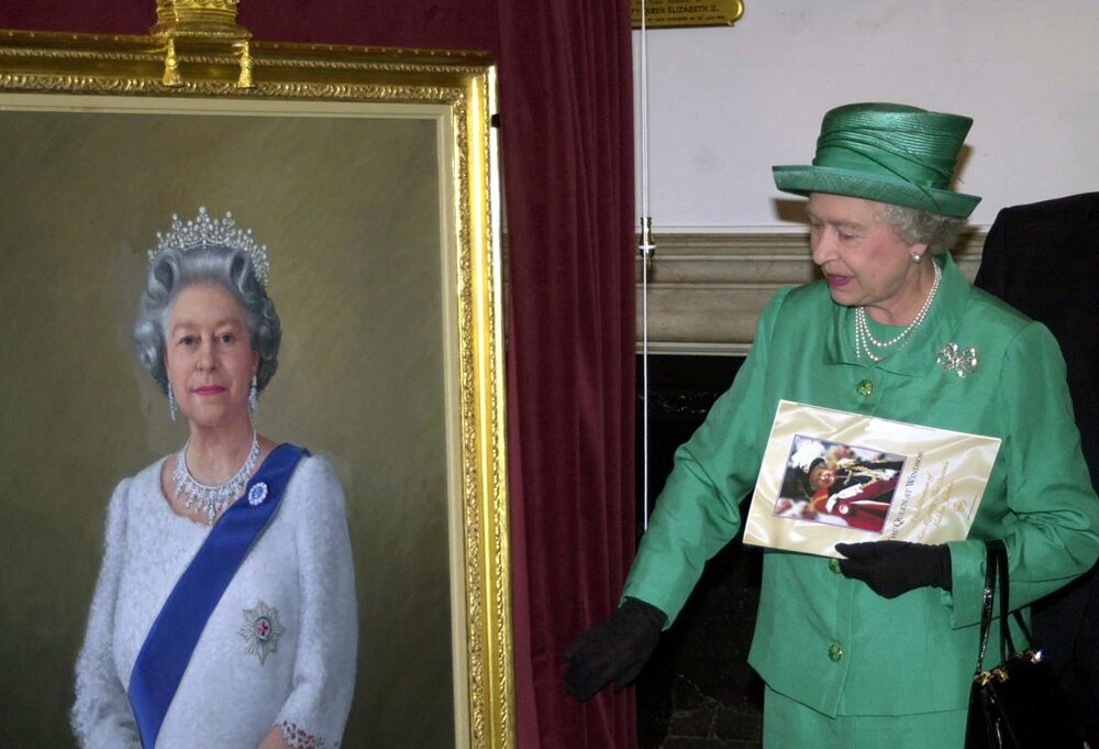 Queen Elizabeth II unveils a portrait of herself by artist Theodore Ramos at the Guildhall in Windsor in 2002, to mark her Golden Jubilee. A 1954 painting of the Queen hangs on the wall in the background.