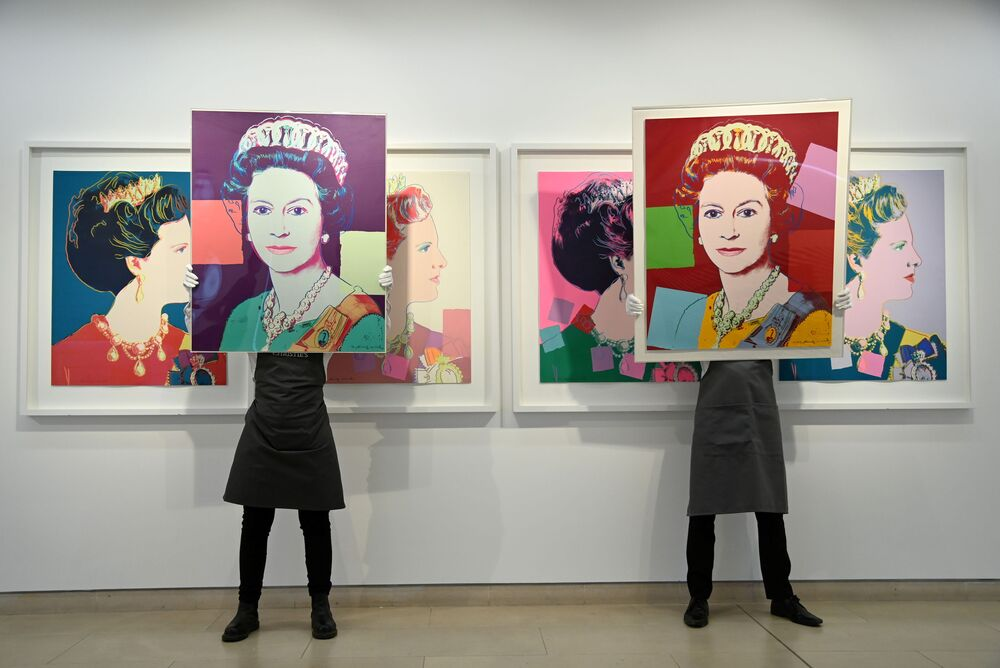 Art handlers pose as they hold two screen prints of 'Queen Elizabeth II' by Andy Warhol in 2021.