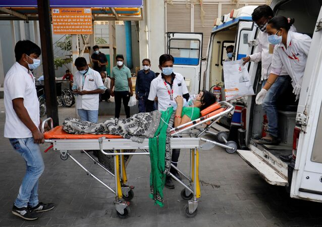 A patient wearing an oxygen mask is wheeled inside a COVID-19 hospital for treatment, amidst the spread of the coronavirus disease (COVID-19) in Ahmedabad, India, April 21, 2021.