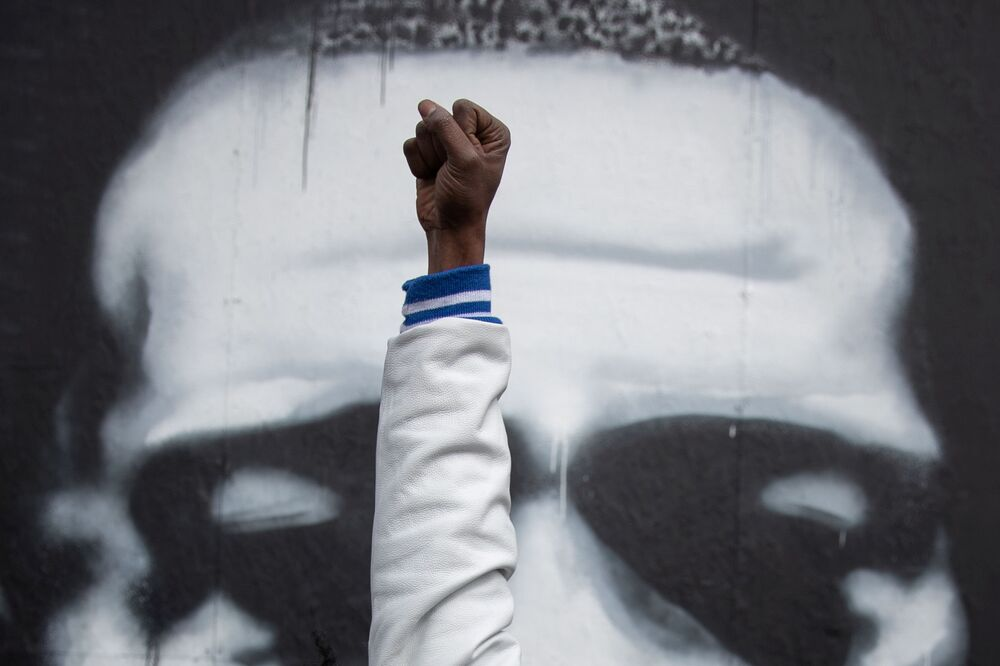 Local resident Michael Wilson raises his fist in front of an image of George Floyd after the verdict in the trial of former Minneapolis police officer Derek Chauvin, found guilty of the death of George Floyd, at George Floyd Square in Minneapolis, Minnesota, US, 20 April 2021.