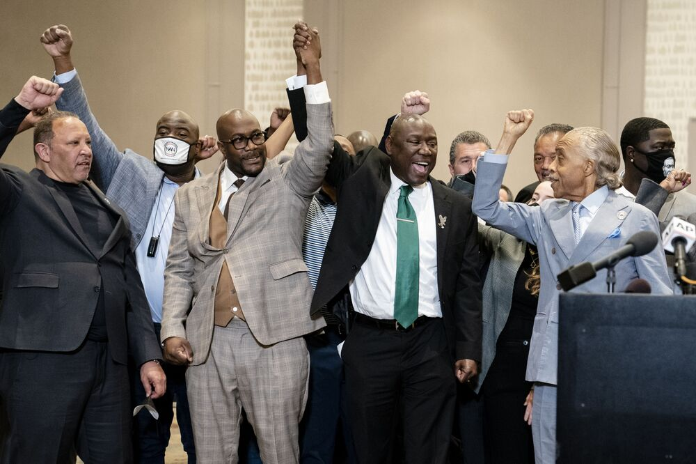 Philonise Floyd, brother of George Floyd, center left, attorney Ben Crump, center right, and the Rev. Al Sharpton, right, raise their hands during a news conference after the murder conviction against former Minneapolis police Officer Derek Chauvin in the killing of George Floyd, Tuesday, 20 April 2021, in Minneapolis.