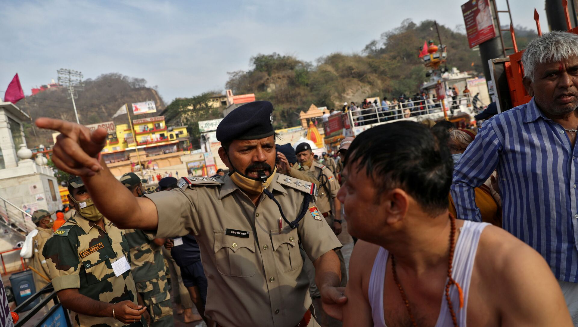 A police officer asks a devotee to leave after he took a holy dip in the waters of river Ganges during Kumbh Mela, or the Pitcher Festival, amidst the spread of the coronavirus disease (COVID-19), in Haridwar, India, April 12, 2021.  - Sputnik International, 1920, 20.06.2021