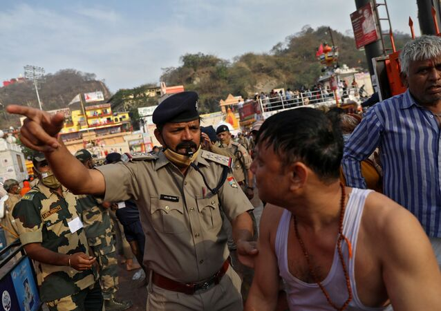 A police officer asks a devotee to leave after he took a holy dip in the waters of river Ganges during Kumbh Mela, or the Pitcher Festival, amidst the spread of the coronavirus disease (COVID-19), in Haridwar, India, April 12, 2021.