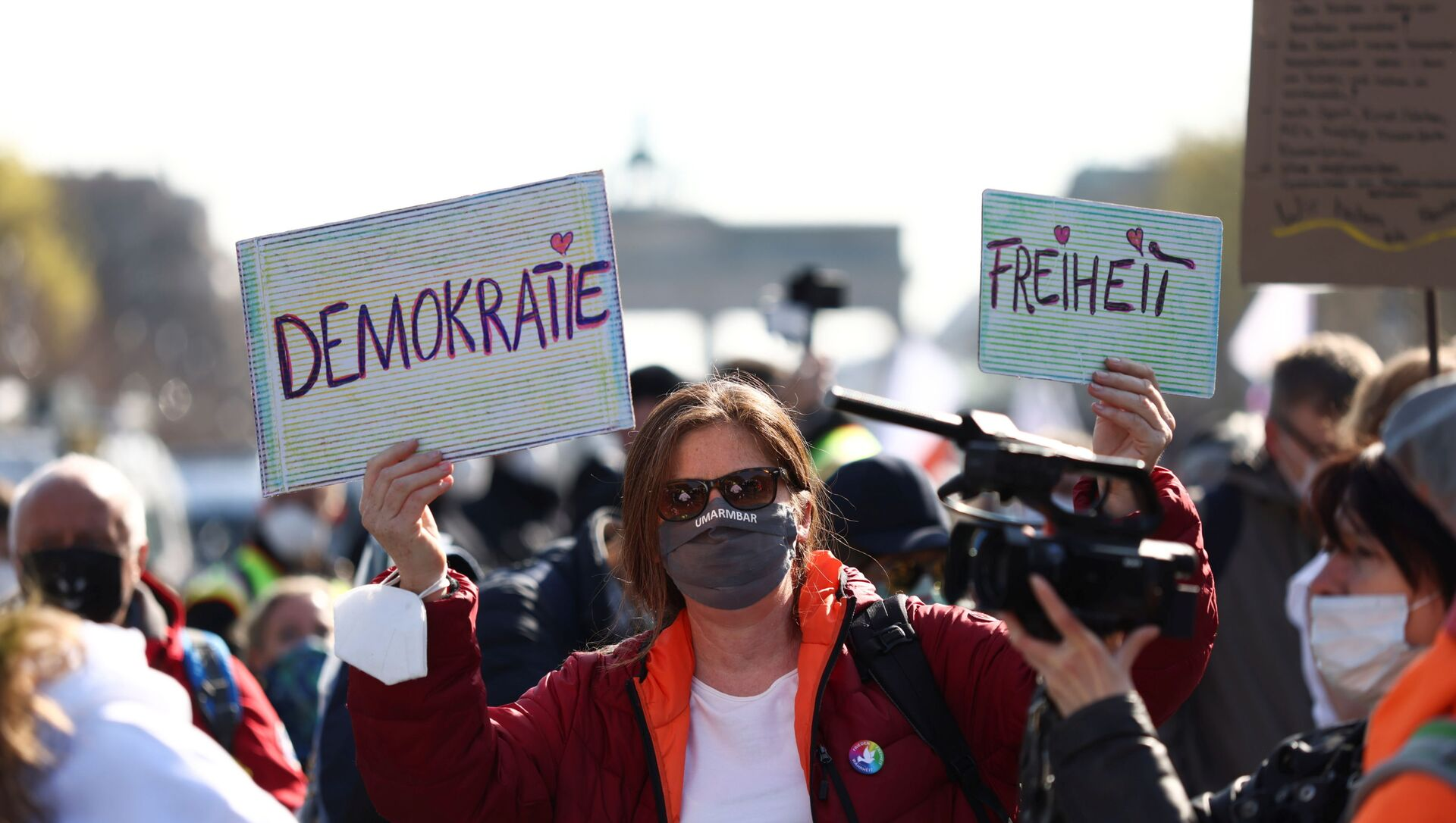 A demonstrator holds up signs reading democracy and freedom during a protest against the government measures to curb the spread of the coronavirus disease (COVID-19), on the day of discussion in the lower house of parliament Bundestag regarding additions for the Infection Protection Act, in Berlin, Germany April 21, 2021 - Sputnik International, 1920, 21.04.2021