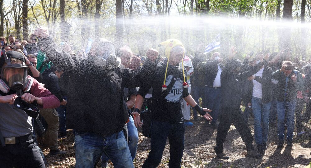 Demonstrators are sprayed with pepper spray during a protest against the government measures to curb the spread of the coronavirus disease (COVID-19), on the day of discussion in the lower house of parliament Bundestag regarding additions for the Infection Protection Act, in Berlin, Germany April 21, 2021